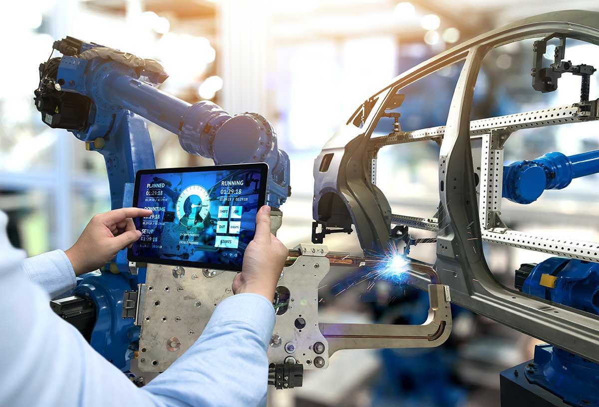 Mitarbeiter vergleicht Produktion mit angezeigten Daten auf einem Tablet